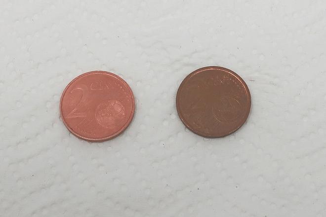 Kupfermünze mit Essig und Kochsalz gereinigt: Die linke Münze ist nach wenigen Sekunden im Essig-Salz-Bad blank, die rechte, angelaufene dient als Vergleich